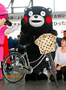 くまモン柄のひったくり防止カバーをつけた自転車に乗ろうとするくまモン